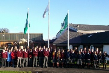 The Environmental group and teachers with the raised flag